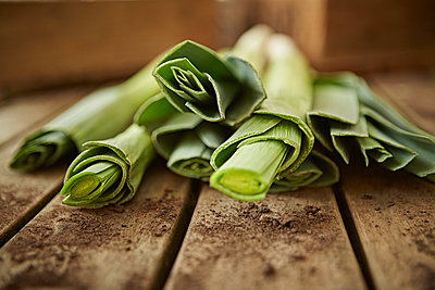 Still life close up fresh, organic, healthy green leek stems on wood - p1023m1485648 by Adam Gault