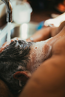 Close-up of man washing hair at barber shop - p1166m1415167 by Cavan Images