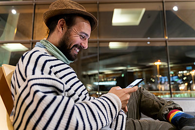 Happy man sitting in airport departure area using smart phone - p300m2179857 by VITTA GALLERY