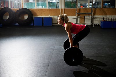 Female crossfitter preparing to lift barbell in gym - p429m1126225f by T2 Images