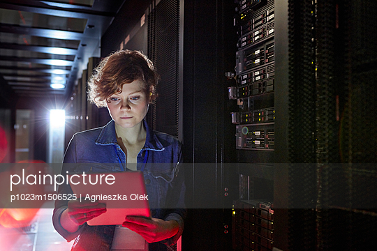 Focused female IT technician using digital tablet in server room