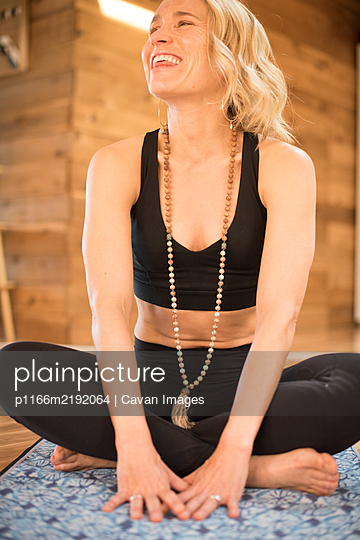 A girl laughs will sitting on her yoga mat. - p1166m2192064 by Cavan Images