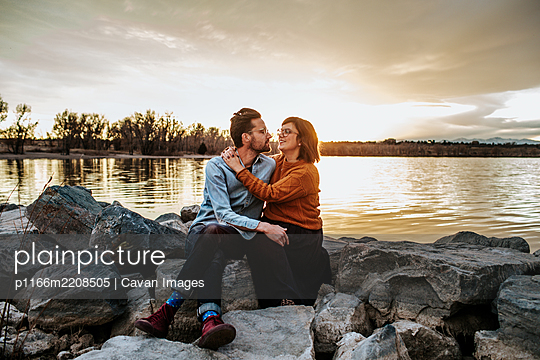 Husband and wife sitting on rocks near a lake on a autumn evening - p1166m2208505 by Cavan Images