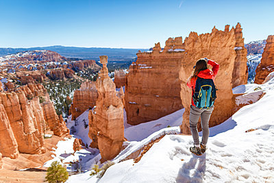 Rear view of hiker standing on snow covered mountain at Bryce Canyon National Park - p1166m1414730 by Cavan Images