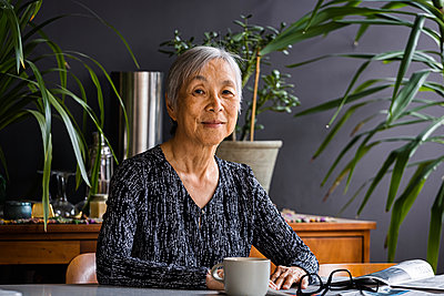Portrait of smiling asian Senior Woman sitting at table at home - p1166m2285615 by Cavan Images