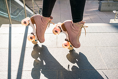 Young woman balancing on roller skates - p1332m1540029 by Tamboly