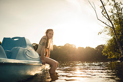 Young woman relaxing on the lake, sitting on boat - p300m2276908 by Gustafsson