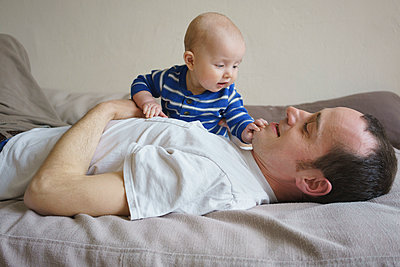 Side view of father lying with son on bed at home - p301m1148387 by Halfdark