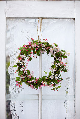 Pretty spring floral wreath made with pink blossom against door with lace curtain. - p349m2167880 by Sussie Bell