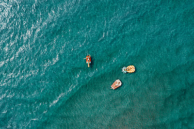 Three women on air mattress in the sea, drone photography - p713m2289221 by Florian Kresse