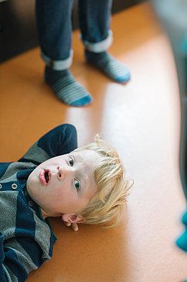 Junge liegt auf Fußboden - p819m1128897 von Kniel Mess