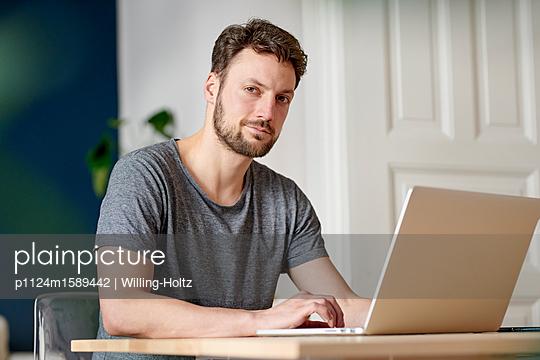 Junger Mann am Laptop zuhause - p1124m1589442 von Willing-Holtz