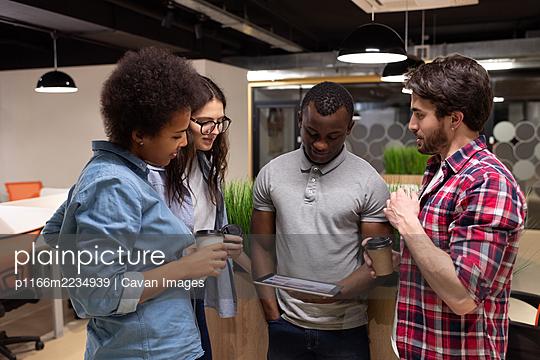 Diverse colleagues watching video on tablet during break - p1166m2234939 by Cavan Images