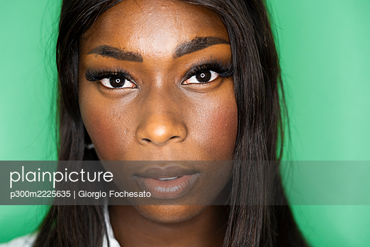 Close-up of woman face against green background - p300m2225635 by Giorgio Fochesato