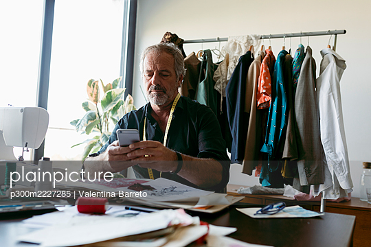 Male costume designer using smart phone while working at table in studio - p300m2227285 by Valentina Barreto