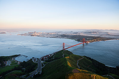 Aerial view of Golden Gate Bridge over San Francisco Bay during sunset - p1166m1164442 by Cavan Images