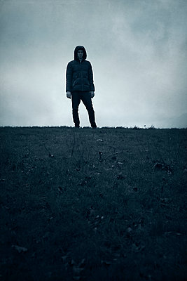 Silhouette of hooded man on hill - p1248m1526419 by miguel sobreira
