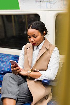 UK, London, portrait of businesswoman in underground train looking at cell phone - p300m1581754 von Mauro Grigollo