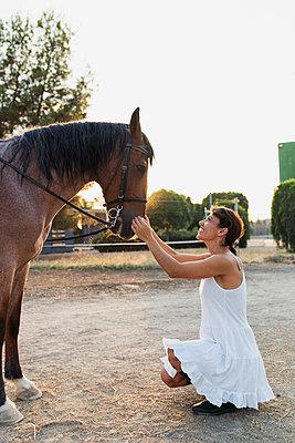 Smiling woman stroking horse - p300m2042133 by Kike Arnaiz