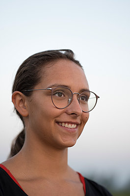 Young woman wearing glasses - p552m2020169 by Leander Hopf