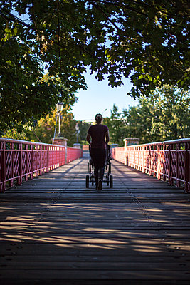 Woman with stoller on bridge - p795m2020887 by Janklein
