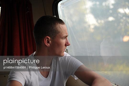 Jugendlicher blickt durch das Fenster seines Wohnwagen - p1468m1584991 von Philippe Leroux