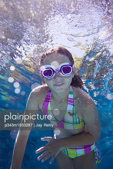 girl swimming towards the camera in a pool, wearing goggles - p343m1033287 by Jay Reilly
