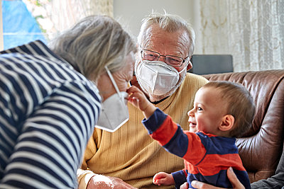 Großeltern mit Maske und Enkelsohn, Portrait - p1146m2187846 von Stephanie Uhlenbrock