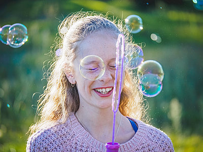 Girl (12-13) blowing bubbles - p1427m1504584 by WalkerPod Images