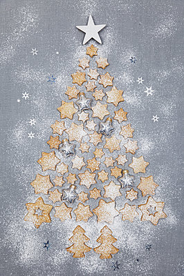Star-shaped biscuits and Christmas baubles forming Christmas Tree on grey background - p300m2012562 by Gaby Wojciech