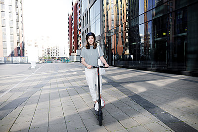 Woman with e-scooter and helmet, modern office buildings in the background - p300m2132100 by Katharina Mikhrin