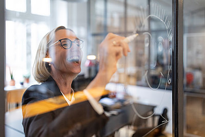 Happy mature businesswoman drawing face on glass pane in office - p300m2154902 by Gustafsson