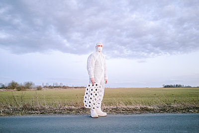 Man wearing protective suit and mask standing on country road with toilet rolls - p300m2170136 by Ekaterina Yakunina