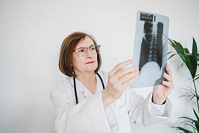 Female doctor examining x-ray image at clinic - p300m2274477 by Eva Blanco