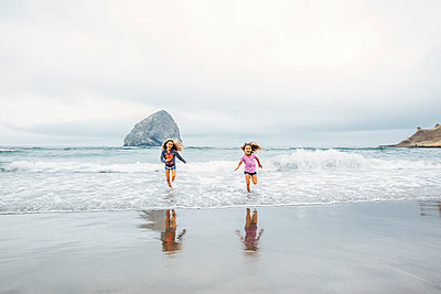 Mixed race sisters running on beach - p555m1311465 by Inti St Clair