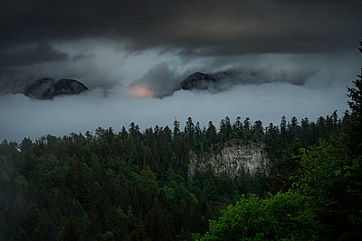 Thunderclouds over deciduous forest and mountain mass, France - p910m2196465 by Philippe Lesprit