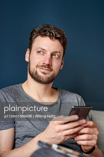 Junger Mann schreibt eine SMS auf dem Smartphone - p1124m1589438 von Willing-Holtz