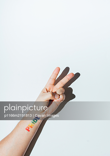 Gay guy's hand with a tattoo that says pride and nail polish. - p1166m2191813 by Cavan Images