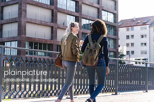 Friends walking on bridge, talking, having fun, rear view - p300m2004766 von Uwe Umstätter