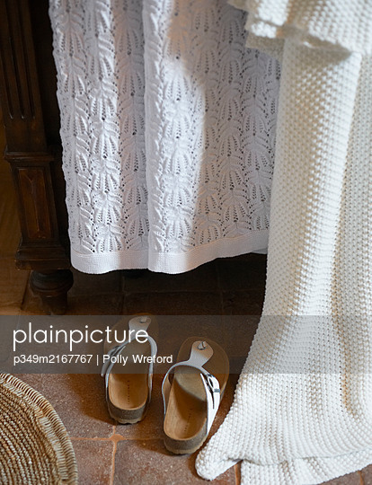 Pair of sandals and white fabrics in bedroom of Sicilian home - p349m2167767 by Polly Wreford
