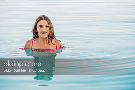 Smiling girl swimming in pool - p623m2068899 by Eric Audras