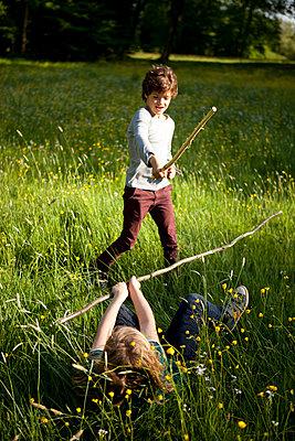 Jungen beim Stockkampf im Park - p1195m1138137 von Kathrin Brunnhofer