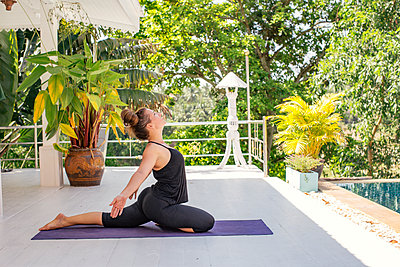 Woman practicing yoga on terrace at the poolside - p300m1587932 by Mosu Media