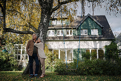 Senior couple in garden of their home in autumn - p300m2156098 by Gustafsson