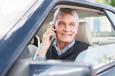 Portrait of smiling senior businessman on the phone in car - p300m2197927 by Daniel Ingold