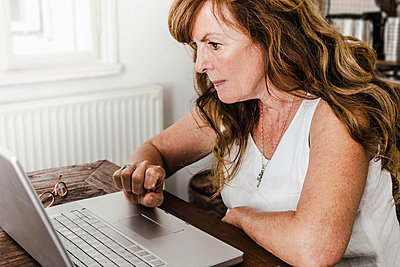 Older woman using laptop in kitchen - p429m659808f by Dan Brownsword