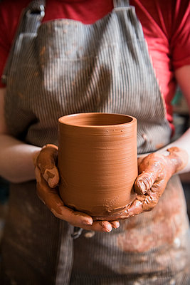Caucasian woman showing pottery cup - p555m1481950 by JGI/Jamie Grill