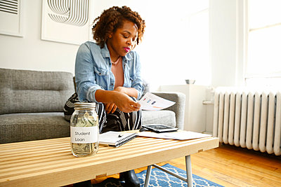 Mixed race woman with student loan reading paperwork - p555m1504196 by Julien McRoberts