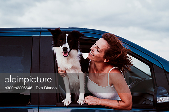 Smiling woman looking at dog while leaning through car window - p300m2206646 by Eva Blanco