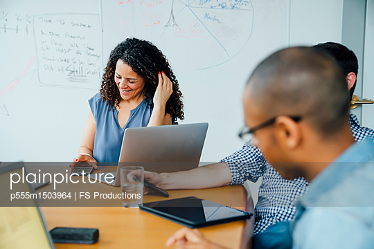 Business people using cell phones in meeting - p555m1503964 by FS Productions